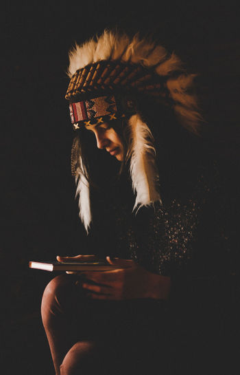 Woman wearing headdress holding book against black background