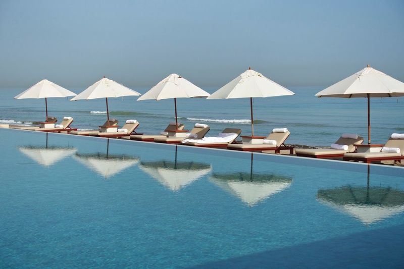 Sun loungers with canopies in row against calm blue sea