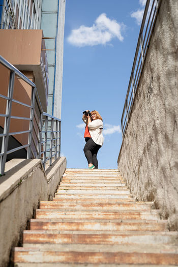 Smiling young woman holding camera standing against steps