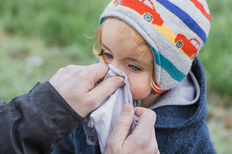 Close-up of person hand cleaning girl nose on land