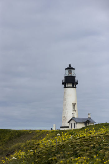 The beautiful lighthouse at Yaquina Head on the Oregon coast is unique in that it still utilizes its first-order Fresnel lens made in 1868. The light source has been automated and updated to electricity, but the lens remains original, providing signal up to 19 miles out to sea from this peninsula jutting about 1-mile out in the pacific. Coast Coastline Lighthouse Pacific Northwest  Landscape Landscape Photography Historic Historical Building Nature Architecture Guidance Tower Sky Land Cloud - Sky Outdoors Wildflowers Pacific Coast Pacific Coast Highway Yaquina Head Yaquina Head Light House Oregon Oregon Coast Ocean Travel Travel Destinations Cloudy Cloudy Day PNWonderland Nature Photography