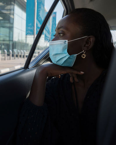 Black woman in the car with face mask on