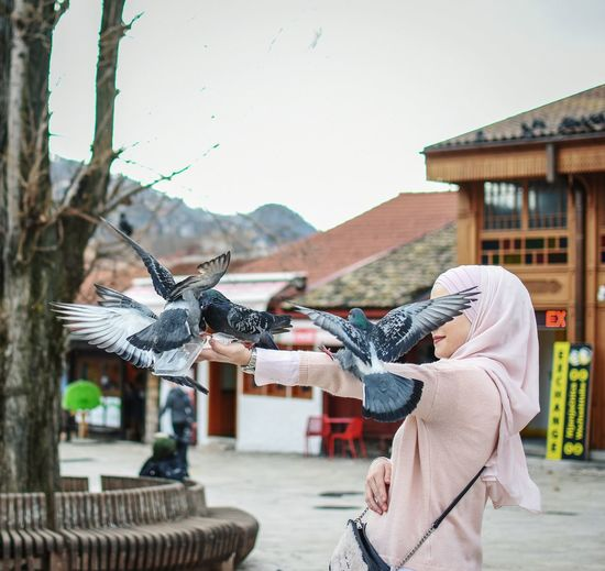 Side view of young woman feeding birds while standing on city street