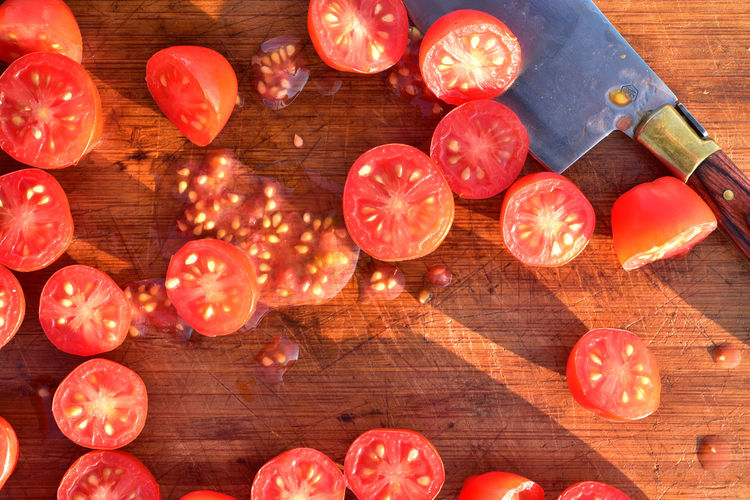 Overhead view of grape tomatoes cut into halves on wood cutting board