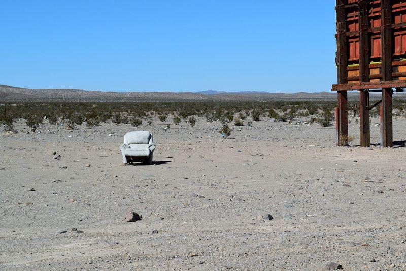 Armchair on landscape against clear sky