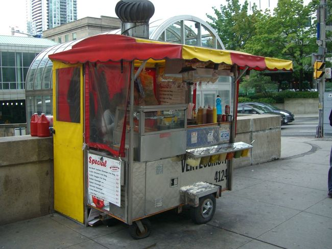 Hot Dog Stand outside Union Station Canada City City Life City Street Composition Food And Drink Full Frame Fun Hot Dog Stand Hot Dogs Incidental People Information Information Sign Lifestyle No People Outdoor Photography Red And Yellow Retail  Shop Small Business Store Tasty Toronto Tourist Destination Tree