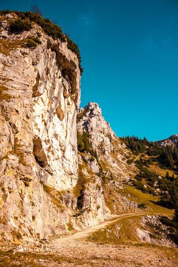 Rock formations on landscape against blue sky
