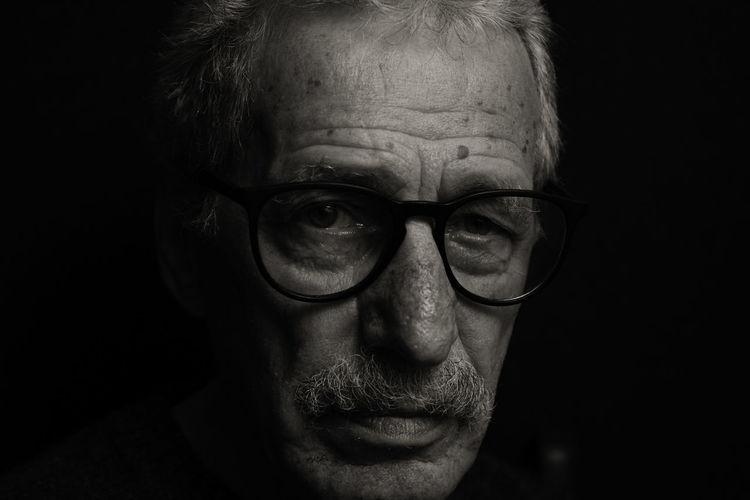 Portrait of man wearing eyeglasses against black background