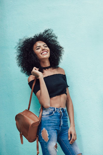 Happy mixed woman with curly hair standing on the street. Female wearing casual clothes in urban background. Lifestyle concept Afro Hairstyles Woman Afrohair Beautiful Woman Beauty Casual Clothing Curly Hair Female Hair Hairstyle Happiness Jeans Leisure Activity Lifestyles Looking At Camera One Person Portrait Real People Smiling Three Quarter Length Wall - Building Feature Women Young Adult Young Women