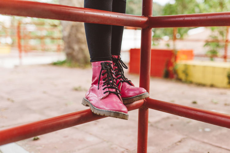 Low section of person wearing red shoes standing on jungle gym