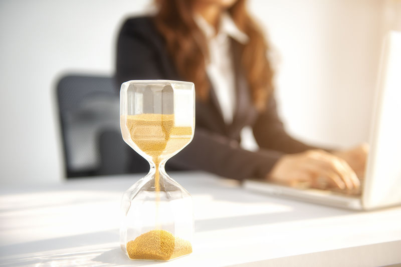 Close-Up Of Hourglass On Desk With Businesswoman Working On Laptop In Background
