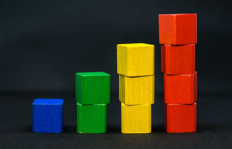 Stack of multi colored toy on wood against black background