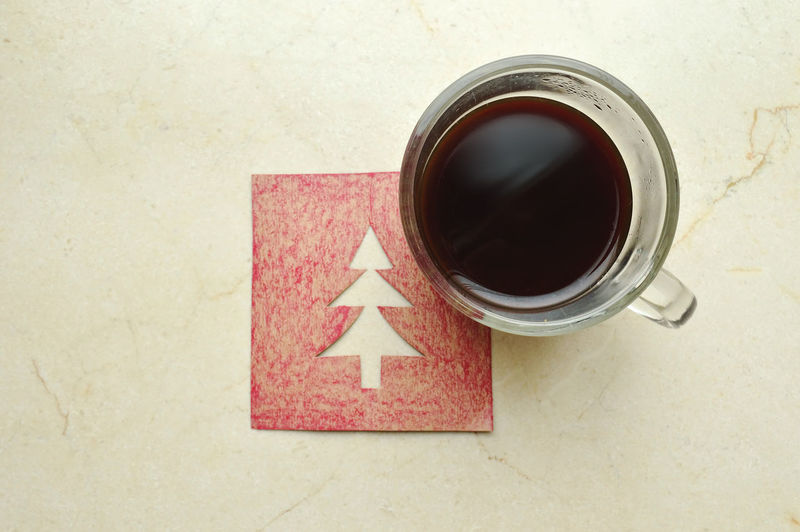 Cup of coffee over a Christmas card with a hollow tree on a marble surcace. Top view Beverage Caffeine Christmas Coffee Hot Christmas Card Christmas Tree Cup Drink Marble Surface