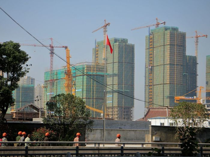 Construction workers head back to their site after lunch in Hangzhou, China. ASIA Chinese Flag Construction Workers Hangzhou,China Workers Architecture Building Exterior Building Industry Built Structure China City Crane - Construction Machinery Day Economic Development Economic Growth Men Modern Outdoors People Real People Sky Skyscraper Workers At Work