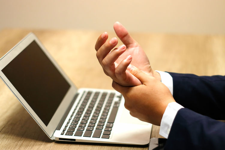 Businessman with wrist pain from using computer, Office syndrome hand pain by occupational disease Technology Computer Human Hand Communication Wireless Technology Laptop Real People Hand Human Body Part One Person Indoors  Men Using Laptop Connection Lifestyles Table Body Part Adult Portable Information Device Finger Surfing The Net Wrist Pain Office Syndrome Occupational Disease