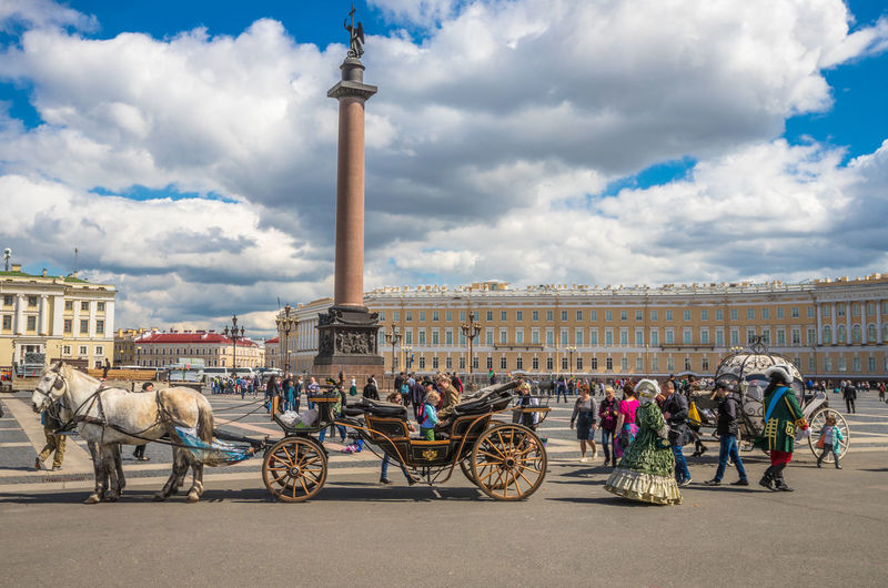 Horse cart in city against cloudy sky