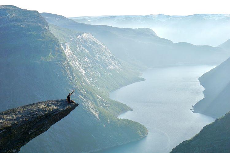 Man sitting on cliff gesturing against mountain range