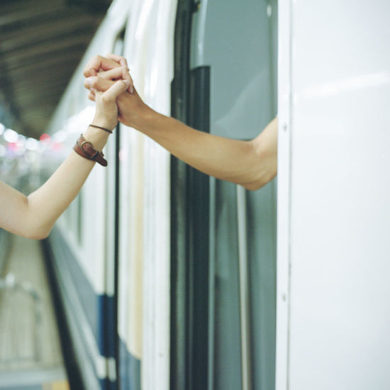 Cropped image of couple holding hands at railroad station platform