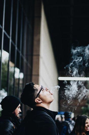 Side of young man emitting smoke
