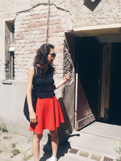 Young woman standing outside building on sunny day