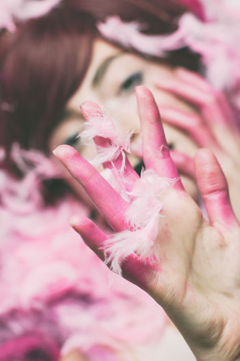 Midsection of woman holding pink petals