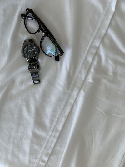 High angle view of eyeglasses on bed