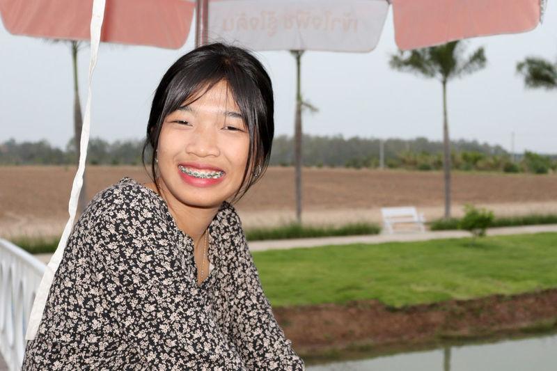 Portrait of smiling teenage girl sitting at cafe