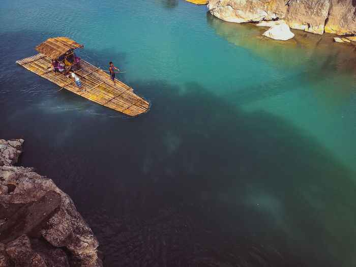 High angle view of people on wooden raft over sea