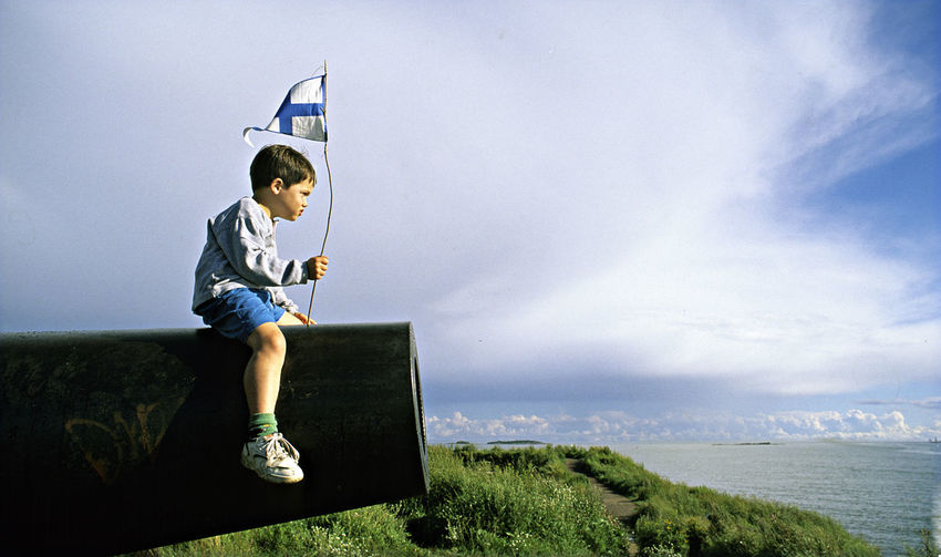 A Boy Sitting On A Gun A Boy With The Finnish Flag Childhood Children Only Day Finland Open See Outdoors Sky The Island Fortress Of Suomenlinna Water an ancient cannon from russian times