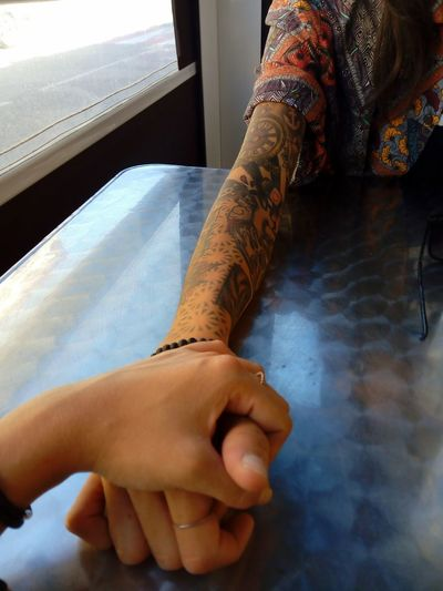 Cropped Image Of Friends Holding Hands At Table
