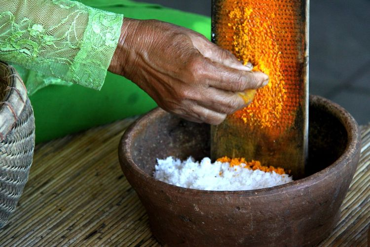 Balinese lady grating tumeric to be mixed with grated coconut to cook yellow rice. Bali Balinese Close-up Coconut Cookies Cooking Culture Cultures Dish Food Grating Human Body Part Lifestyles People Person Spice Spices Traditional Tumeric Working Hands At Work