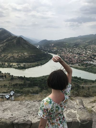 Rear view of woman against mountains and sky