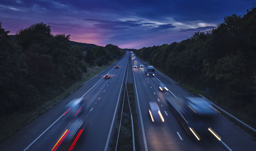 High angle blurred motion of cars on road against cloudy sky at dusk