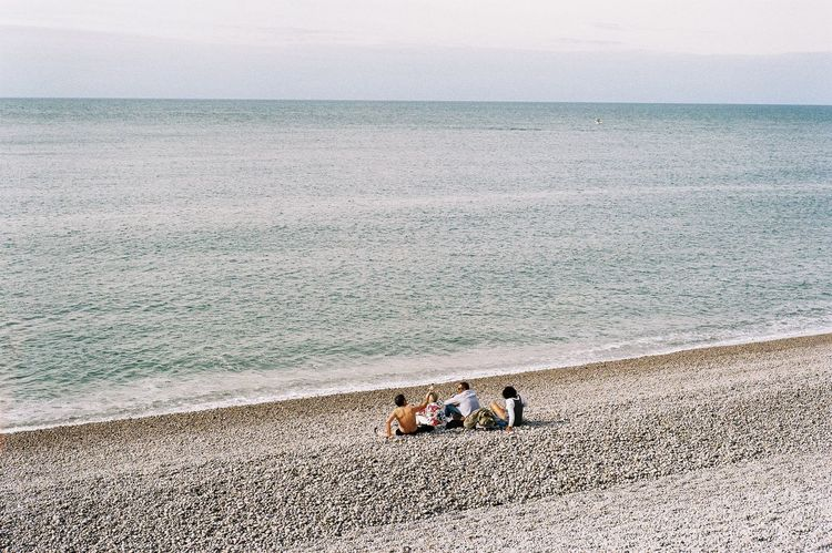 Film Photography EyeEm Selects Sea Beach Horizon Over Water Sand Water Togetherness Day Relaxation Sitting Tranquility Vacations Outdoors Nature Leisure Activity Men Group Of People Women Sky Scenics Friendship
