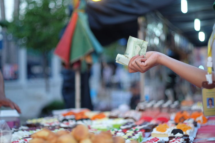 Close-Up Of Hand Holding Paper Currency At Market Stall