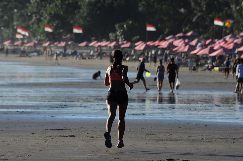 People running on beach against sky