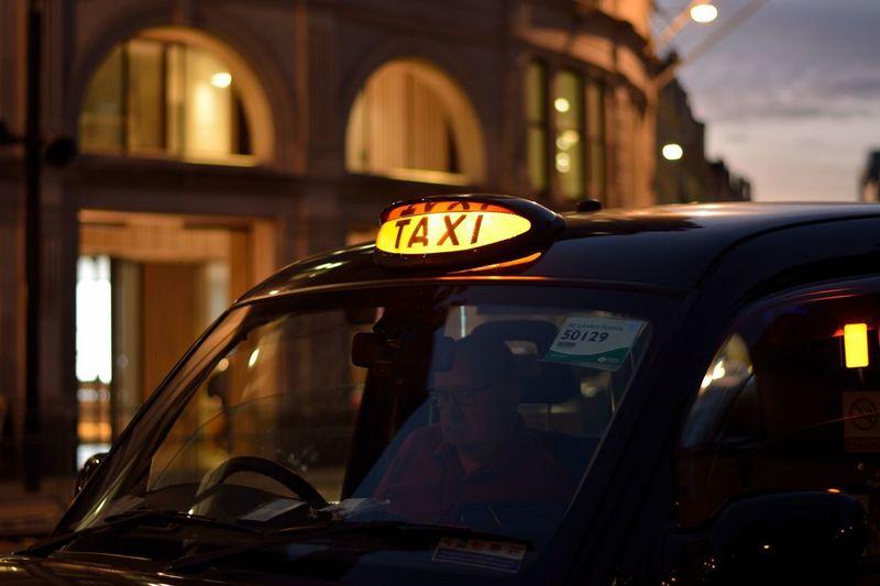 Reflection of illuminated car in city at night