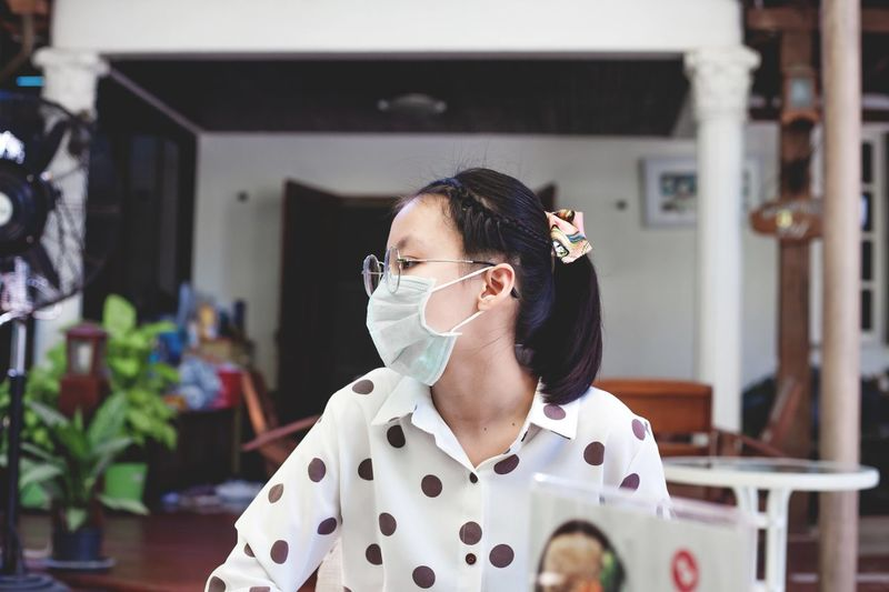 Girl looking away while wearing mask at home