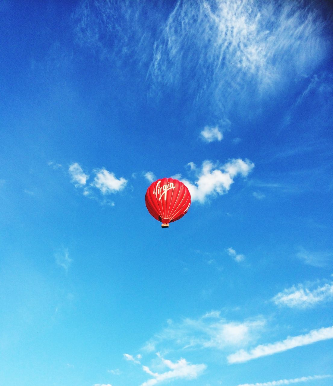 sky, low angle view, red, blue, cloud - sky, flying, mid-air, adventure, day, outdoors, nature, no people, beauty in nature, parachute