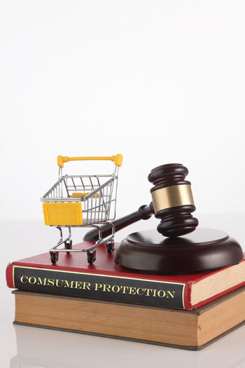 Close-Up Of Hammer And Gavel With Books And Shopping Cart Against White Background