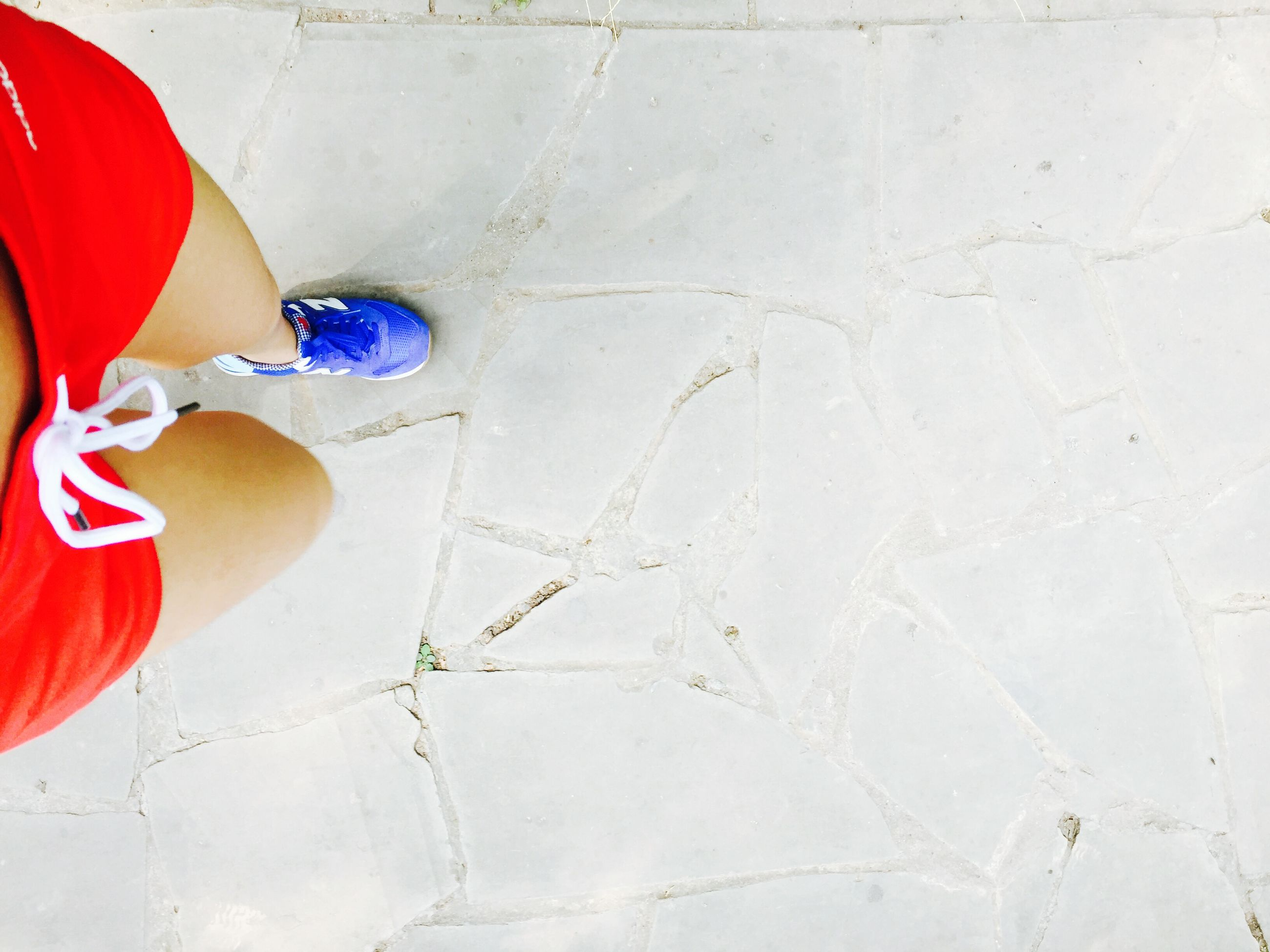 red, tiled floor, wall - building feature, shoe, high angle view, tile, low section, flooring, footwear, indoors, day, street, sidewalk, wall, no people, cobblestone, paving stone, white color, absence
