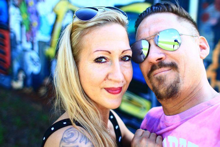 Portrait Of Smiling Mid Adult Couple Against Graffiti