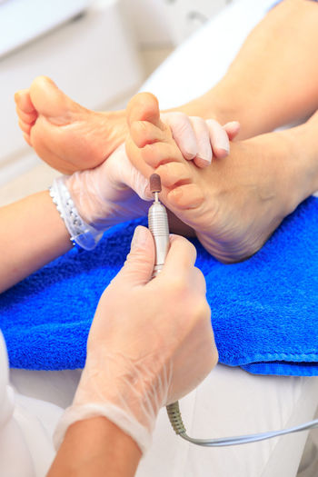 closeup of the feet by receiving of pedicure at the beauty salon Beautiful, Beauty, Body, Care, Closeup, Cosmetics, Fashion, Feet, Female, Finger, Fingernails, Foot Care, Hand, Hands, Nail, Nails, Natural, Pedicure, Polish, Professional, Salon, Skin, Spa, Treatment, White, Woman, Yellow, Young