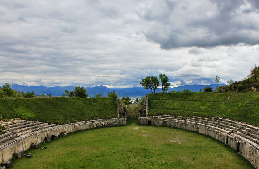 www.head-eye-heart.com Abruzzo AlbaFucens Ancient Anphitheater Architecture Beauty In Nature Built Structure Cloud Cloud - Sky Cloudy Grass Growth History Landscape Mountains Nature Outdoors Overcast Roman Ruins Scenics Sky The Past Tourism Travel Destinations