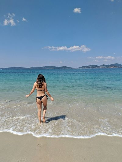 Full length of woman wading in sea against sky