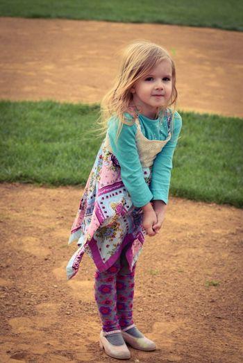 Full length portrait of girl standing on baseball field