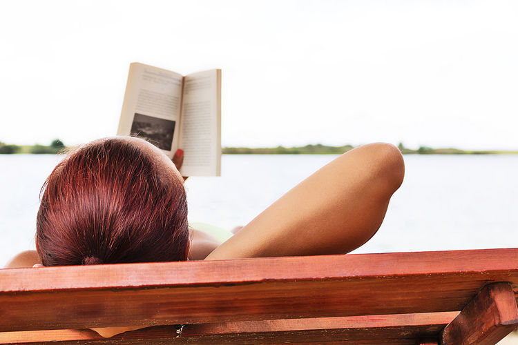 Rear view of woman relaxing on open book