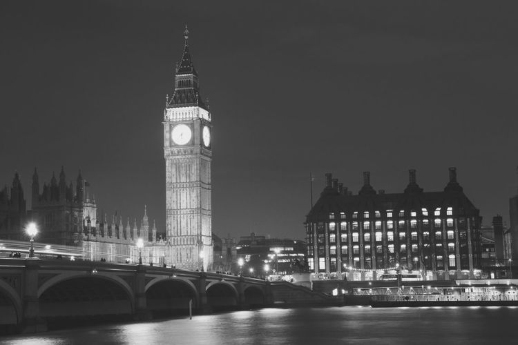 Illuminated big ben by thames river against sky