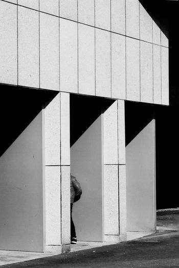 Side view of woman walking by building in city