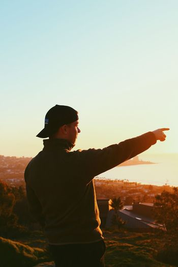 Side view of young man standing against sky during sunset